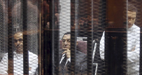 Egypt's ousted President Hosni Mubarak sits next to his sons Gamal and Alaa inside a dock at the police academy on the outskirts of Cairo