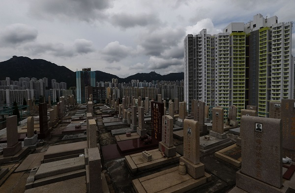 Headstones stand at a cemetery surrounded by residential flats in Hong Kong