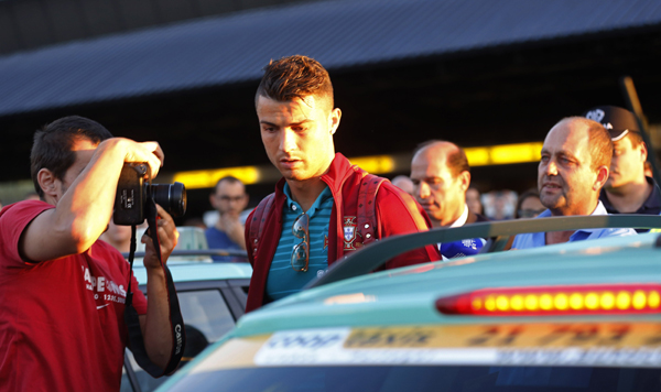 Portugal's Cristiano Ronaldo prepares to enter a taxi after returning from the 2014 World Cup in Brazil with the national soccer team, at Lisbon airport
