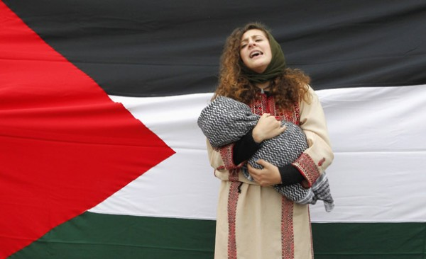 A female member of the Palestine community shouts slogans for peace in Gaza in front of a Palestine flag, during a rally in Valparaiso, northwest of Santiago