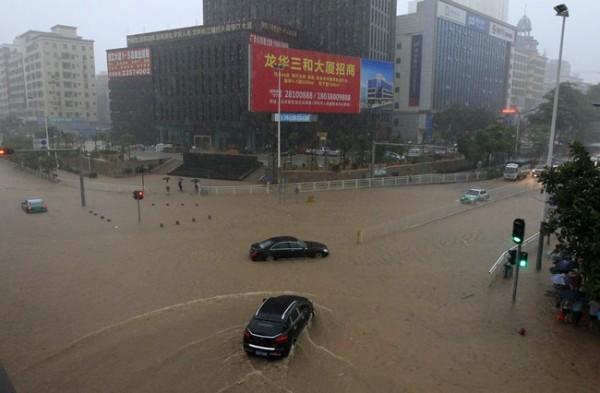 Car drives down a flooded street amid heavy rainfall in Shenzhen