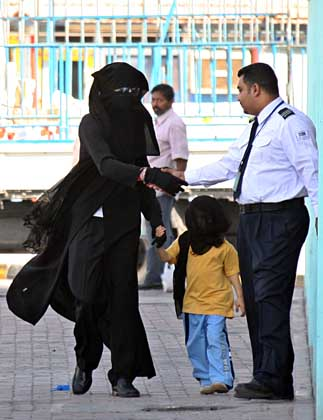 Jackson wearing traditional women veil and gown leaves shopping mall in Bahrain
