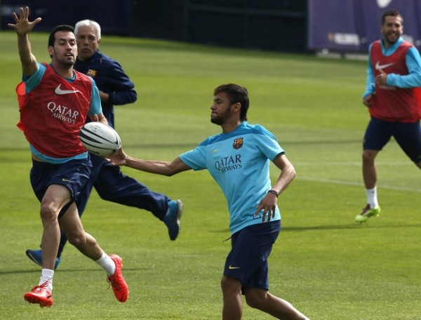 Barcelona's Neymar plays with a rugby ball with teammate Sergio Busquets during a training session at Ciutat Esportiva Joan Gamper training camp, near Barcelona