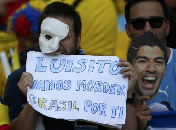 Fans of Uruguay hold a mask of Suarez and a banner before their 2014 World Cup round of 16 game against Colombia at the Maracana stadium in Rio de Janeiro