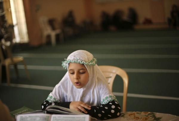 Palestinian girl takes part in Koran memorization lesson on first day of holy fasting month of Ramadan at a mosque in Gaza City