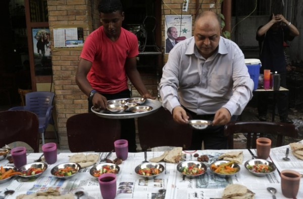 """Volunteers distribute iftar, the breaking of fast meal, for free at """"charity tables"""" on a street during the first day of Ramadan, in Cairo"""
