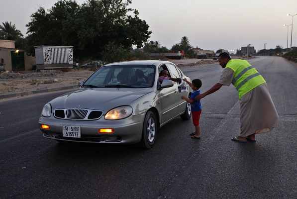 A man with his child distributes packed meals for the breaking of fast to members of the public during the Islamic holy month of Ramadan in Tripoli