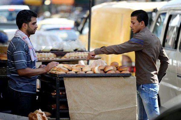 A man buys traditional bread before iftar, the breaking of fast meal, during the Muslim fasting month of Ramadan in Al-Medan district in Damascus July 1, 2014.  REUTERS/Omar Sanadiki (SYRIA - Tags: FOOD RELIGION SOCIETY)