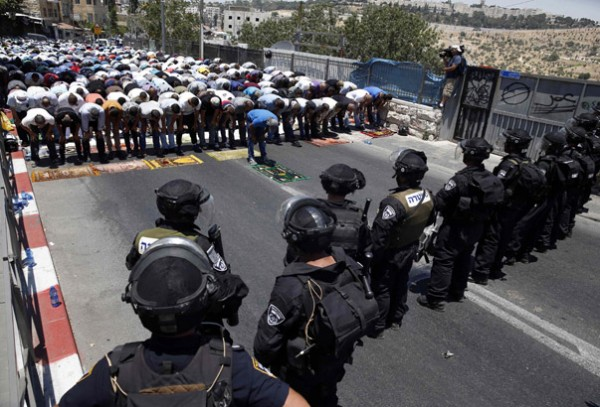 Palestinians pray on the first Friday of Ramadan as Israeli policemen stand guard in East Jerusalem