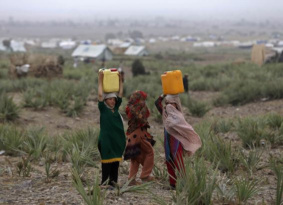 Displaced Pakistani  girls carry drinking water on their heads at a refugee camp in Khost  province