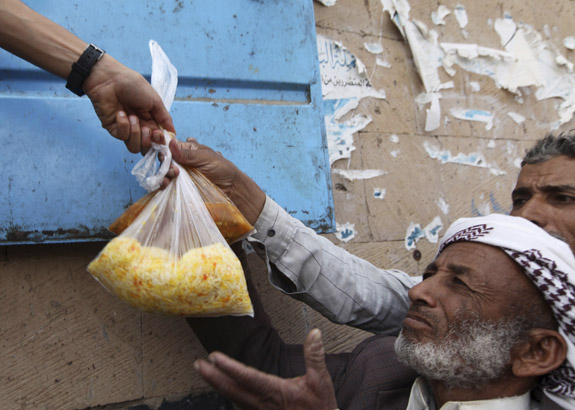 Volunteers distribute food rations to the needy during the holy fasting month of Ramadan at a mosque in Sanaa