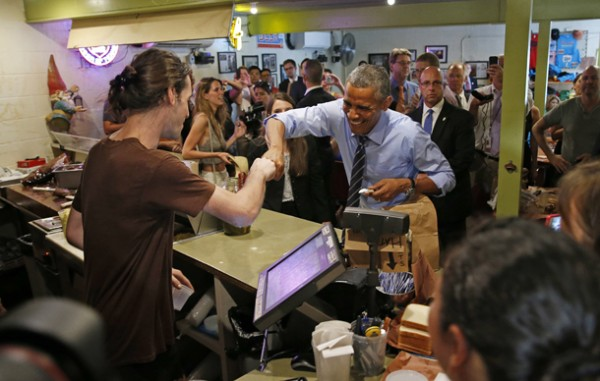 U.S. President Obama fist bumps the cashier after paying for his order at Franklin Barbecue in Austin