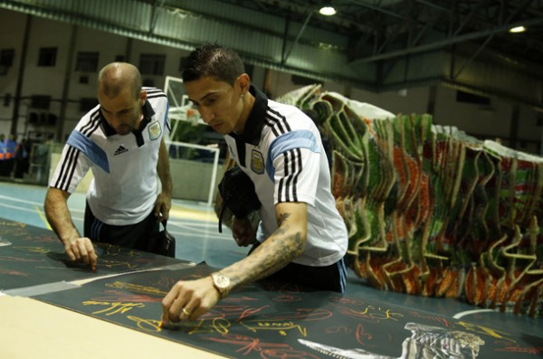 "Argentina's di Maria and Palacio sign banners with the image of a sculpture by Swiss artist Pflugi called ""The Seeds of Victory"" in Rio de Janeiro"
