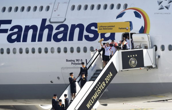 Germany's captain Lahm holds up the World Cup trophy as he leaves the plane followed by Schweinsteiger and team mates after landing at Tegel airport in Berlin