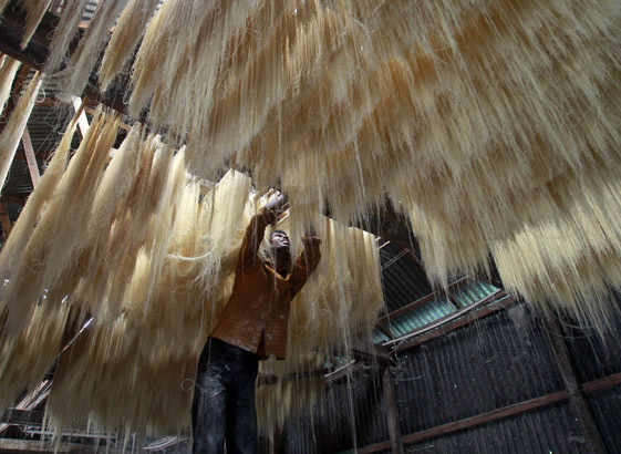 A worker hangs strands of vermicelli, a specialty eaten during the Muslim holy month of Ramadan, to dry at a factory on the outskirts of Agartala