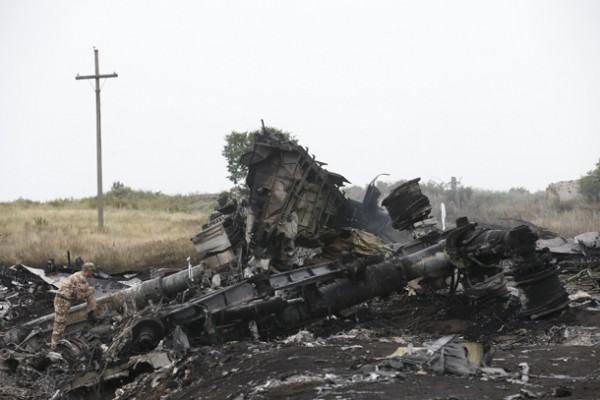 A pro-Russian separatist stands at the crash site of Malaysia Airlines flight MH17 before a visit by OSCE monitors, near the settlement of Grabovo in the Donetsk region