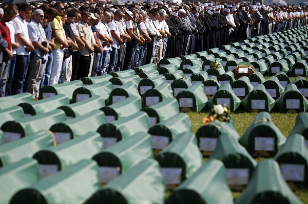 Bosnian Muslims pray near the coffins of relatives during a mass funeral for bodies found in a mass grave, in Kozarac