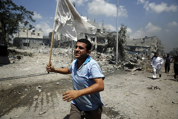 A Palestinian man runs with a white flag during fighting in Gaza City