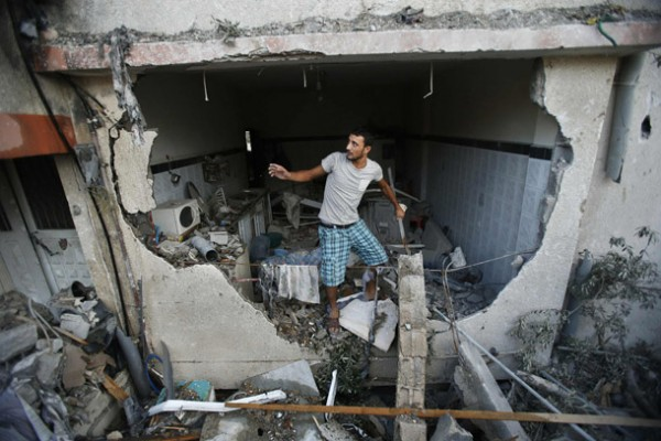 A Palestinian man inspects a house which police said was damaged in an Israeli air strike, in Gaza City