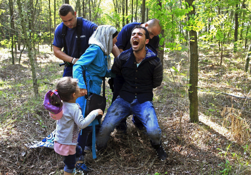 "Hungarian policemen detain a Syrian migrant family after they entered Hungary at the border with Serbia, near Roszke, August 28, 2015. REUTERS/Bernadett Szabo          SEARCH ""YEAREND 2015: MIGRANT CRISIS"" FOR ALL 55 PICTURES"