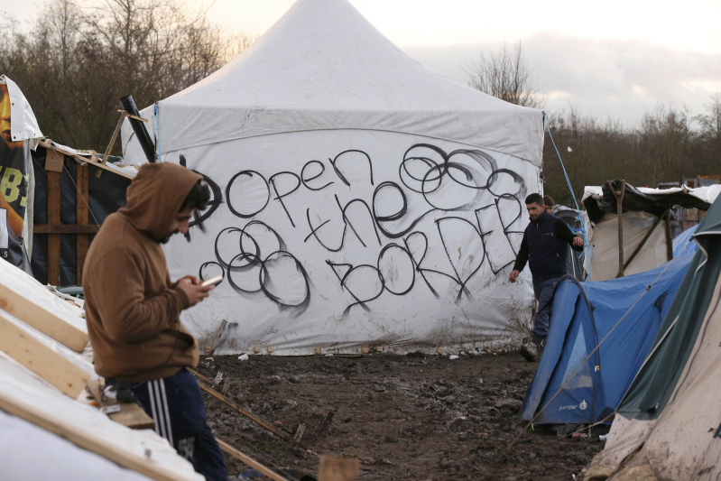 "Migrants stand in the mud near a tent with the message, ""Open the Border"" that is located in a field called the Grande Synthe jungle, a camp of makeshift shelters where migrants and asylum seekers from Irak, Kurdistan and Syria gather in Grande-Synthe, France, December 29, 2015.  REUTERS/Pascal Rossignol"