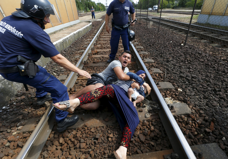 "Hungarian policemen stand by the family of migrants as they wanted to run away at the railway station in the town of Bicske, Hungary, September 3, 2015. REUTERS/Laszlo Balogh     SEARCH ""YEAREND 2015: MIGRANT CRISIS"" FOR ALL 55 PICTURES"