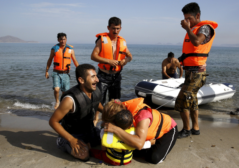 "An Iranian migrant cries next to his son and wife moments after a small group of exhausted migrants from Iran arrive by paddling an engineless dinghy from the Turkish coast (seen in the background) at a beach on the Greek island of Kos August 15, 2015.  REUTERS/Yannis Behrakis     SEARCH ""YEAREND 2015: MIGRANT CRISIS"" FOR ALL 55 PICTURES"