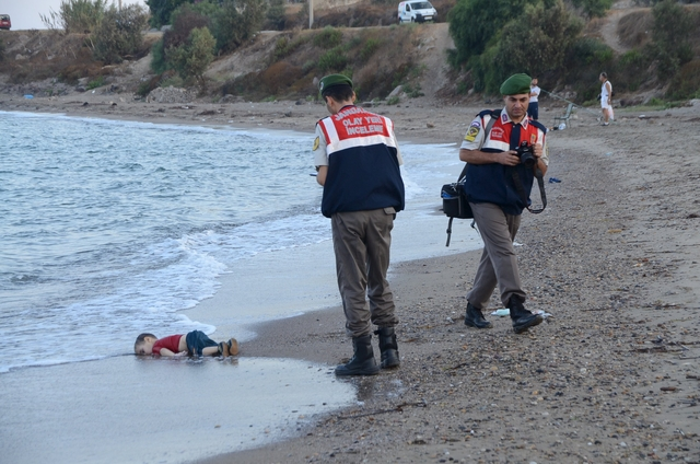 ATTENTION EDITORS - VISUAL COVERAGE OF SCENES OF DEATH OR INJURY A Turkish gendarmerie stands next to a young migrant, who drowned in a failed attempt to sail to the Greek island of Kos, as he lies on the shore in the coastal town of Bodrum, Turkey, September 2, 2015. At least 11 migrants believed to be Syrians drowned as two boats sank after leaving southwest Turkey for the Greek island of Kos, Turkey's Dogan news agency reported on Wednesday. It said a boat carrying 16 Syrian migrants had sunk after leaving the Akyarlar area of the Bodrum peninsula, and seven people had died. Four people were rescued and the coastguard was continuing its search for five people still missing. Separately, a boat carrying six Syrians sank after leaving Akyarlar on the same route. Three children and one woman drowned and two people survived after reaching the shore in life jackets.  REUTERS/Nilufer Demir/DHA  ATTENTION EDITORS - NO SALES. NO ARCHIVES. FOR EDITORIAL USE ONLY. NOT FOR SALE FOR MARKETING OR ADVERTISING CAMPAIGNS. TEMPLATE OUT. THIS IMAGE HAS BEEN SUPPLIED BY A THIRD PARTY. IT IS DISTRIBUTED, EXACTLY AS RECEIVED BY REUTERS, AS A SERVICE TO CLIENTS. TURKEY OUT. NO COMMERCIAL OR EDITORIAL SALES IN TURKEY.