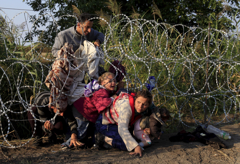 "Syrian migrants cross under a fence as they enter Hungary at the border with Serbia, near Roszke, August 27, 2015.   REUTERS/Bernadett Szabo      SEARCH ""YEAREND 2015: MIGRANT CRISIS"" FOR ALL 55 PICTURES"