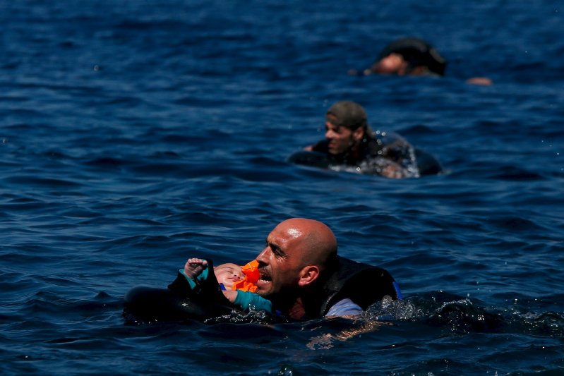 "A Syrian refugee holding a baby in a lifetube swims towards the shore after their dinghy deflated some 100m away before reaching the Greek island of Lesbos, September 12, 2015.    REUTERS/Alkis Konstantinidis    SEARCH ""YEAREND 2015: MIGRANT CRISIS"" FOR ALL 55 PICTURES          TPX IMAGES OF THE DAY"