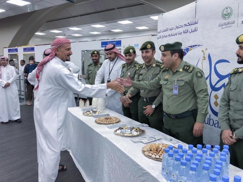 شاهد بالصور.. جوازات مطار الملك عبدالعزيز تعايد المسافرين بالحلوى والهدايا