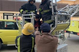 إنقاذ طفل احتجز خارج سياج نافذة بعنيزة