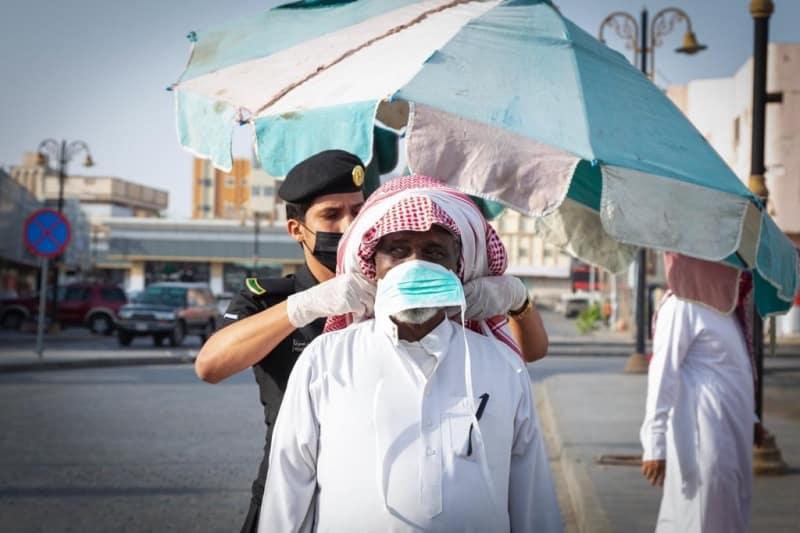 رجل أمن يساعد مواطنًا مسنًّا في ربط كمامته الطبية - المواطن