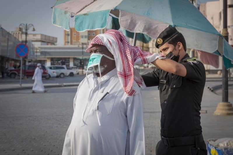 رجل أمن يساعد مواطنًا مسنًّا في ربط كمامته الطبية