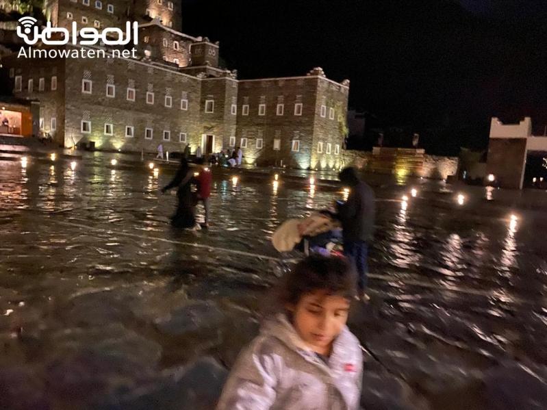 شاهد زوار قرية رجال ألمع يستمتعون بالتجول تحت زخات المطر
