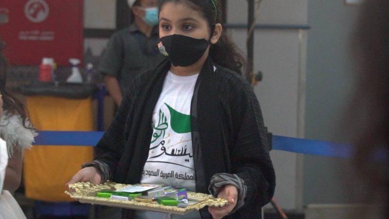 طلاب يوزعون الإعلام في مطار جازان