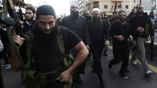 Armed supporters of Salafist leader al-Assir escort him during a funeral in Sidon