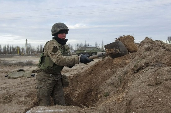 Ukrainian serviceman digs a trench at a checkpoint near the village of Strelkovo