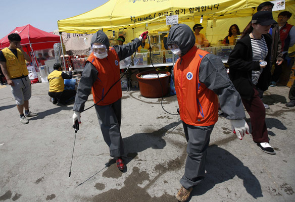 Women wearing protective suits spray antiseptic solution around volunteers' tents at a port in Jindo