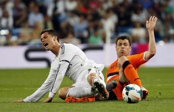 Real Madrid's Ronaldo grimaces as he is tackled by Valencia's Fuego during their Spanish first division soccer match in Madrid