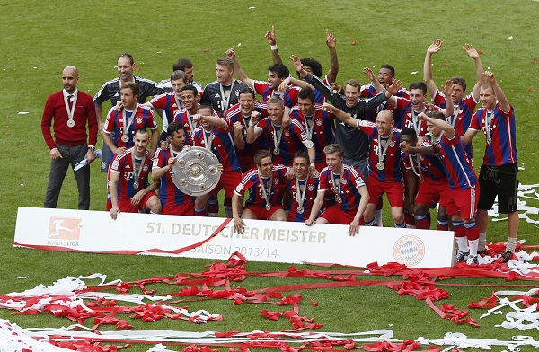 Bayern Munich players hold up German soccer trophy as they celebrate winning Bundesliga title in Munich