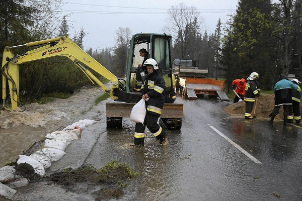 Firefighters construct barriers by the side of the road during flooding in Koscielisko