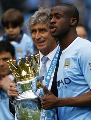 Manchester City's Toure and manager Pellegrini celebrate after winning the English Premier League trophy following their soccer match against West Ham United in Manchester
