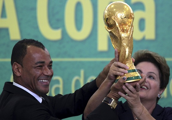 Former Brazilian soccer player Cafu and Brazil's President Dilma Rousseff hold up the World Cup trophy during a ceremony at the Planalto Palace in Brasilia