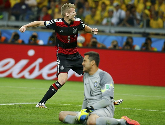 Germany's Schuerrle celebrates near Brazil's goalkeeper Julio Cesar  after scoring during their 2014 World Cup semi-finals in Belo Horizonte