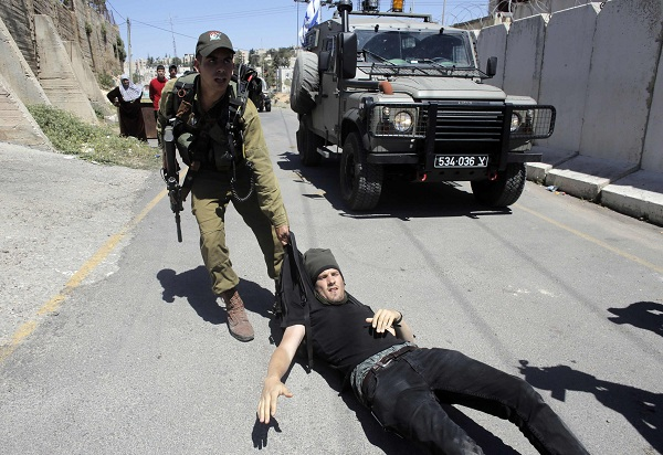 An Israeli soldier drags a foreign activist on the ground during clashes near a house disputed over by Israeli settlers and Palestinians in the West Bank city of Hebron