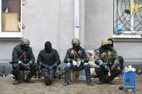 Pro-Russian armed men sit near the police headquarters in Slaviansk