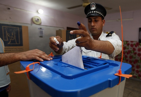 A traffic policeman casts his vote into a ballot box during early voting for the parliamentary election in Baghdad