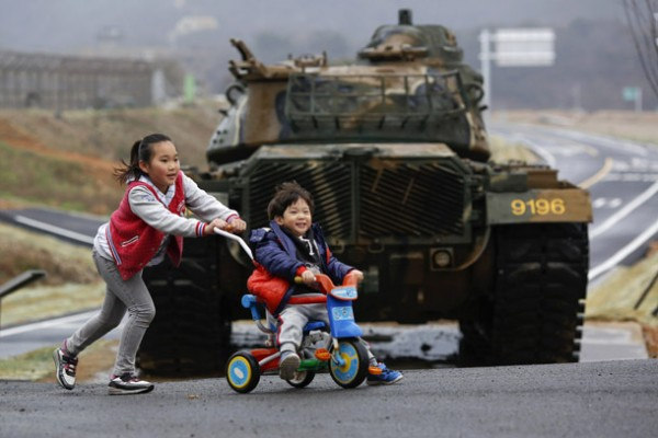 File photo of children playing in front of tank on island of Baengnyeong, which lies on South Korean side of Northern Limit Line, in Yellow Sea