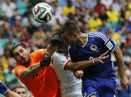Bosnia's Ibisevic heads the ball next to Iran's goalkeeper Haghighi and Sadeghi during their 2014 World Cup Group F soccer match at the Fonte Nova arena in Salvador